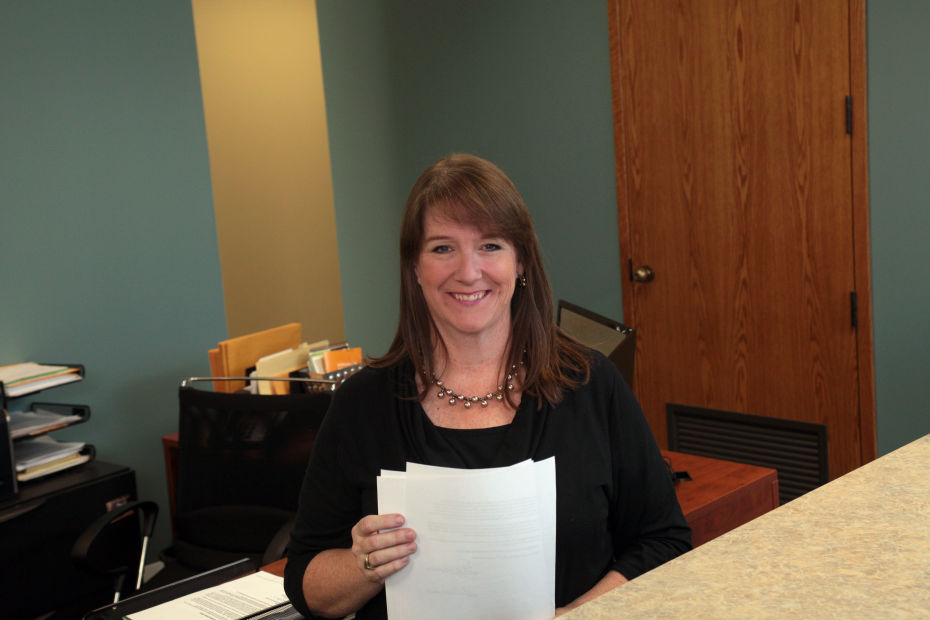 Laura South, Legal Assistant, with documents, standing behind law office counter. A photo.